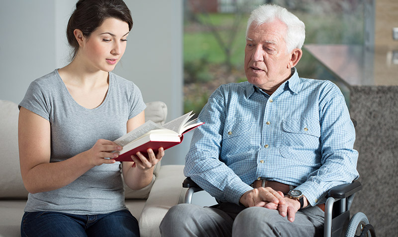 Senior care assistant reading a book to an elder man